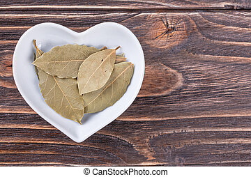 bay leaf in a bowl in the form of heart on a wooden...