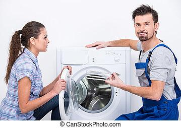 Washing - Repairman is repairing a washing machine for...