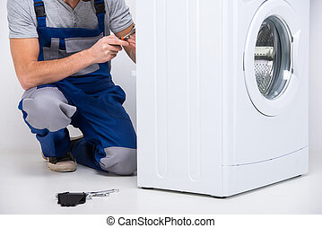 Washing - Repairman is repairing a washing machine on the...