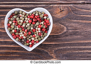 peppercorn mix in a bowl in the form of heart on a wooden...