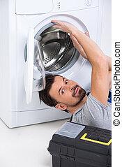 Washing - Repairman is repairing a washing machine on the...