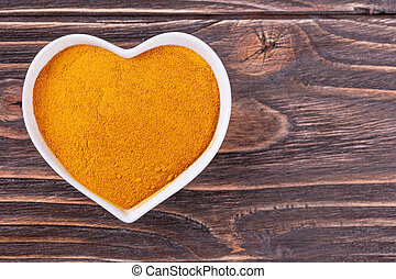turmeric spice in a bowl in the form of heart on a wooden...
