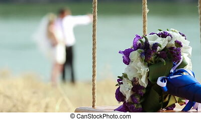 Flowers on seesaw and couple - Wedding bouquet on seesaw...