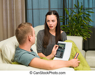 home finances - caucasian couple sitting on couch at home...
