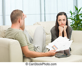 home finances - worried couple doing their accounts at home