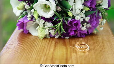 Wedding bouquet and rings on seesaw