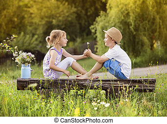 Cute kids in love - Cute boy and girl in love. They sitting...