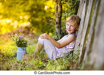Cute little girl with flowers laughing - Little blonde girl...