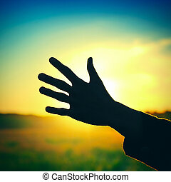 Hand on Sunset Background - Toned Photo of a Hand Silhouette...