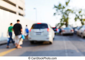 People and car in parking area - Abstract blurred people and...