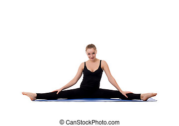 Beautiful young girl doing gymnastic splits on mat