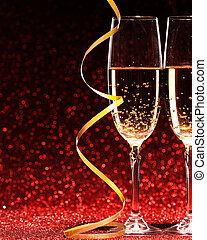 glasses of champagne with yellow holidays ribbons, on red...