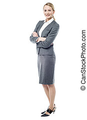 Smiling business woman, folded arms. - Full length image of...