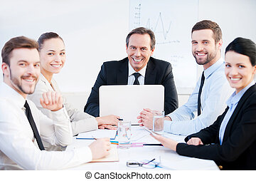 Confident business team. Group of confident business people in formalwear sitting at the table together and smiling