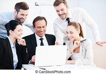 Business discussion. Group of confident business people in formalwear sitting at the table together and discussing something while looking at the laptop