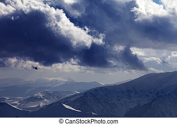 Helicopter in winter mountains and cloudy sky. Ski resort...