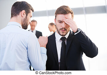 Bad news. Rear view of young businessman consoling his...