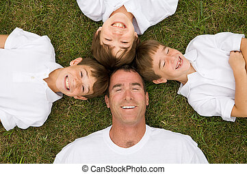 Father and Three Sons Laying in Grass Laughing