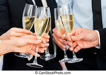 Cheers to success. Close-up of business people holding...