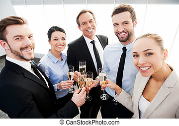 Toast to success. Group of business people toasting with champagne and smiling while standing close to each