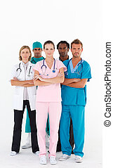 Serious team of doctors looking at the camera with folded...