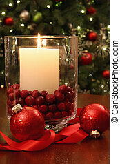 Christmas candle buring brightly in front of tree