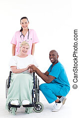 Doctors with a patient in a wheel chair smiling at the camera