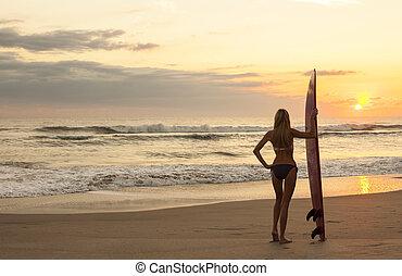 Woman Bikini Surfer & Surfboard Sunset Beach - Rear view of...