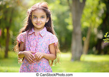 Portrait of hispanic girl in sunny park - Portrait of...