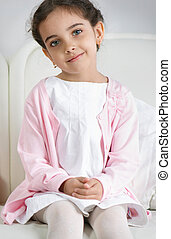 Portrait of pretty little girl sitting on sofa