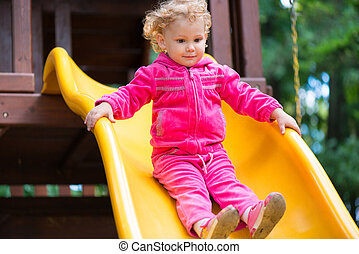 Curly blonde girl sliding at playground - Curly haired...