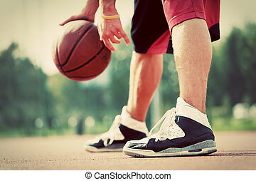 Young man on basketball court dribbling with ball....