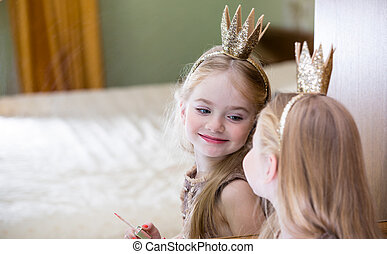 The little princess looks in the mirror