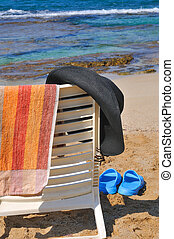 Hat and towel on a chair by the sea