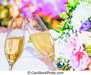 champagne flutes with golden bubbles on wedding flowers...