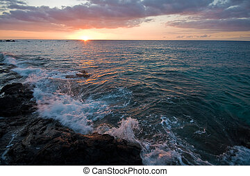 Sunset on Hawaii Big Island - waves breaking on rocky shore...