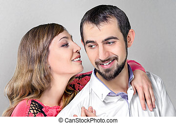 woman whisper to boyfriend putting a hand on his shoulder -...