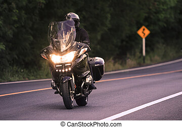 young man riding big motorcycly on asphalt road use for men...