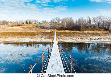 Pedestrian suspension bridge of steel and wood over the...