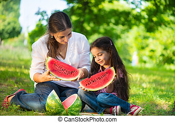 Happy indian family eating watermelon in park