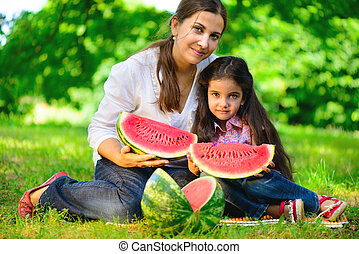 Happy indian family eating watermelon
