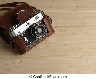Old retro camera on background of wooden boards