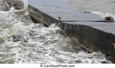 Cement stone pier brokes storm waves