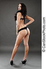 Sexy lingerie model on gray background, full length