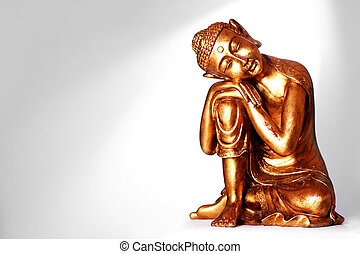 Buddha statue - A Buddha statue resting, in front of a gray...