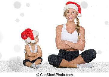 Mom and daughter doing yoga under falling snow - Mom and...