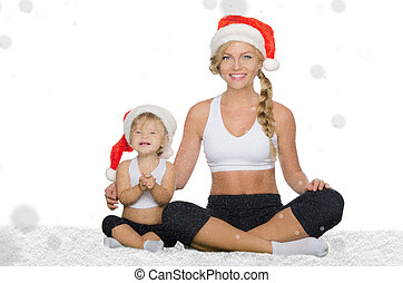 woman with child doing yoga in Christmas hats under snow
