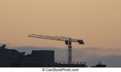 Crane on building site at night brown sky background