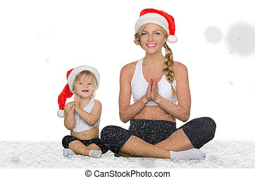 woman with child doing yoga under falling snow - woman with...