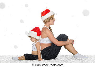 Mother and daughter sitting on snow in Santa hats and...